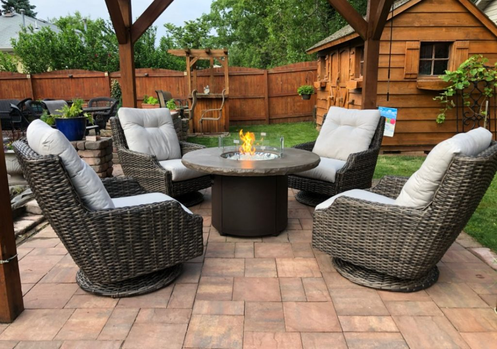 A set of 4 pieces of patio furniture adorn a green fenced-in lawn.