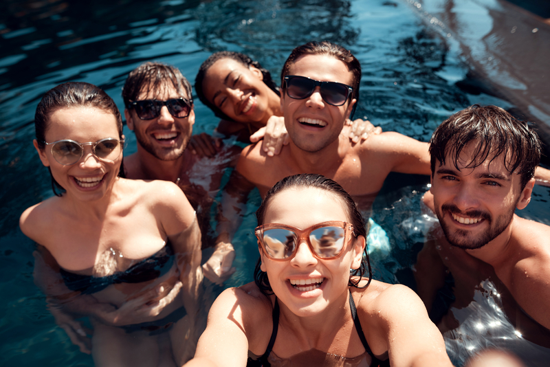 Friends pose for a selfie at an adults-only pool party.