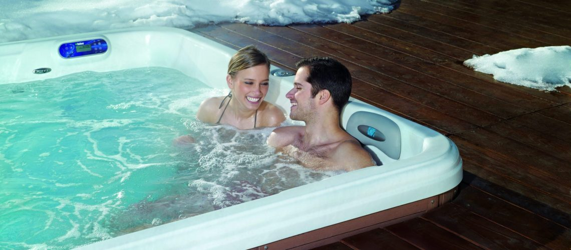 Man and woman enjoying a warm soak in a TidalFit swim spa